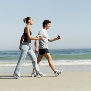 side view of a couple walking on the beach